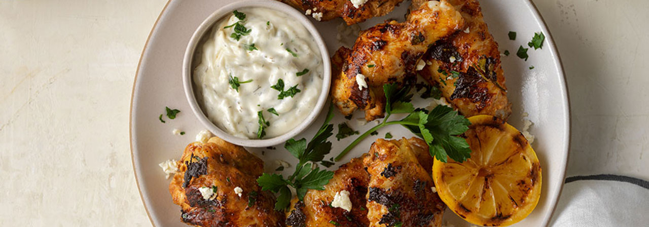 Yogurt-Marinated Grilled Chicken Wings with Tzatziki Sauce and Charred Lemons